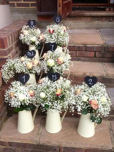 Shabby chic table centres in cream jugs with hand made chalk board table numbers