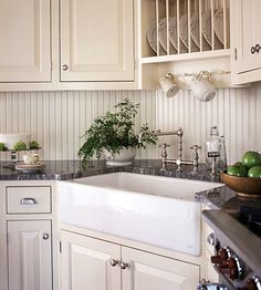 Country French Corner Sink A plate rack above this corner sink makes putting away dishes a breeze. The faucet and apron-front sink echo the traditional style of the cabinetry and the beaded-board backsplash.