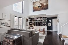 Beautiful built-ins give the main living area plenty of storage, while the oversized artwork emphasizes the vertical scale of the room.  #refinery29 http://www.refinery29.com/2016/04/108928/alexis-bledel-vincent-kartheiser-brooklyn-heights-penthouse-apartment#slide-4
