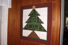 My quick and easy Log Cabin tree.  It has tiny gold jingle bells in the center of each block.  Except when the cat gets hold of it!