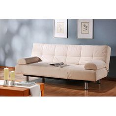 Futons to replace our worn out couches add a utilitarian as well as modern look and the light color brightens up our dark living room.