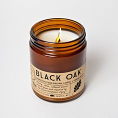 Candle Scent: Oakwood + Laurel + Sandalwood Hand poured into a straight sided amber glass jar with a rustic embossed woodgrain label and black screw on cap. Made with an all natural soy wax blend, USA