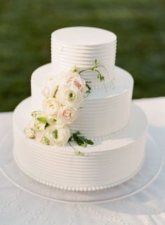 Three tier textured ranunculus topped wedding cake: http://www.stylemepretty.com/2016/11/15/a-white-on-white-wedding-design-made-for-the-classic-couple/ Photography: KT Merry - https://www.ktmerry.com/