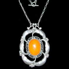 This is not contemporary - image from a gallery of vintage and/or antique objects. GEORG JENSEN (1866-1935)  A silver and amber set pendant.