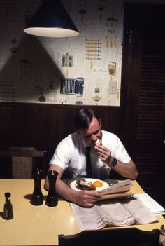 """Not originally published in LIFE. Neil Armstrong and his customary late dinner over the Wall Street Journal, March 1969. """"Neil worked late. The first thing he did when he got home — the family had always eaten already — he sat down at the table and looked up the stock market numbers."""""""