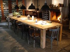 industrial lights and a very, very big wooden table by oudebouwmaterialen.nl