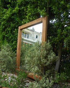 another mirror with custom reclaimed wood frame set in garden