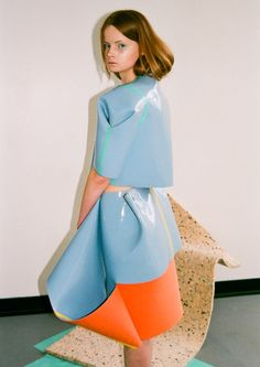 Sheets of latex-covered foam folded to create glossy geometric clothes in strange shapes.