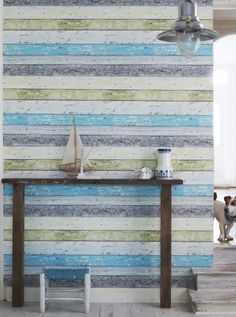 From ikeafamilylivemagazine.com, the wall of this English cottage is sided in wood plank and painted in colors of the sea to create a cozy, beachy feel.