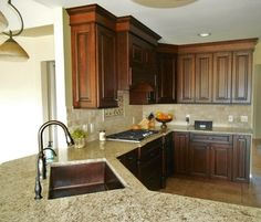 Giallo Ornamental with Dark Cherry Cabinets and Travertine Backsplash, Copper Sink is a Bonus!