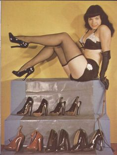 Bettie Page, posing with a selection of high-heeled fetish shoes.    (Source: spaceghostzombie)