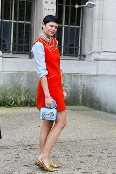 オレンジのミニドレスに、デコラティブなネックレスを合わせて