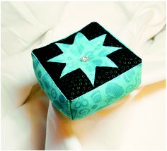 This is a teal tone-on-tone fabric with black star points.  We used a jewel button that sparkles.