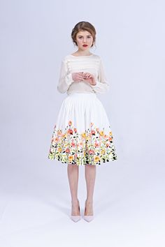 Give your wedding a twist with this Floral Bridal Skirt. This 100% cotton skirt features an original flower print created by Canadian artist Genevieve Godbout. Lined and gently pleated, this retro skirt is reminiscent of 1950s style, but comes equipped with pockets and a small zipper to reflect modern needs. This midi skirt is delicate and feminine while also being bold and vibrant. A modern bride looking to put a personal spin on traditional bridal attire will dazzle guests with this…