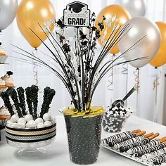 DIY a gold coin centerpiece for your sweet treats spread! Simply use a spray centerpiece & combine it with a grad sign cutout on a skewer. Fill a clear container with Sixlets®, gold chocolate coins and the spray centerpiece. Done!