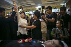 Paula Bronstein/Getty Images MOURNING: A woman held up her arm on Monday in Bangkok as hundreds of mourners paid their respects to Suthin Taratin, a antigovernment leader killed by gunmen Sunday. Mr. Suthin was killed and several others were injured amid clashes between rival political factions in the Thai capital as antigovernment protesters blockaded polling stations.