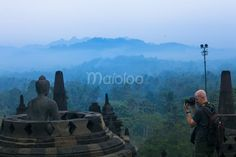 Seorang wisatawan asing sedang mengabadikan salah satu arca yang terbuka di Candi Borobudur. (Benedictus Oktaviantoro/Maioloo.com)