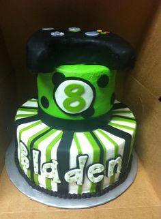 Black and neon green birthday cake topped with a video game
