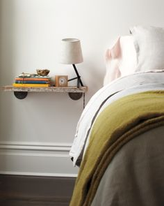 Shelf-Turned-Bedside Table  It's possible to maximize space in even the tiniest of rooms. From clever hideaways to hanging shelves, here's how to make the most of your living space.     To save floor space and create a sense of airiness in a bedroom, use a bracketed shelf instead of a nightstand.