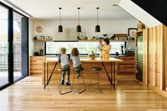 Black accents, from door frames to pendants, contrast with the kitchen's blackbutt floor and joinery.