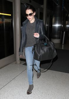 Emilia Clarke kept her style palette dark at LAX. She paired a gray sweater with a leather biker jacket, skinny denim, and cap-toe booties.  Image Source: FameFlynet