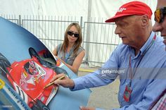 Austrian former Formula One racing driver and three-time F1 World Champion Nikki Lauda gives autographs in a paddock area prior to the qualifying round of Formula One's Malaysian Grand Prix at the Sepang International Circuit in Sepang on March 24, 2012. AFP PHOTO/ Prakash SINGH