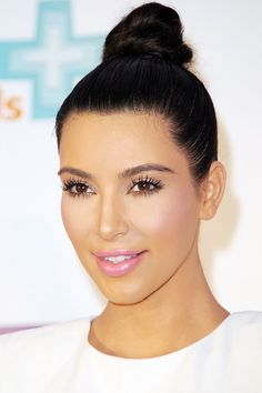 A sleek top knot and a pink flush (this is Kim's version of minimal makeup) looks fresh and pretty for spring.   - HarpersBAZAAR.com