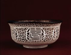 Porcelain reticulated bowl with everted rim, lined with silver on the interior. The bowl has white glaze. There is an openwork design consisting of trellis patterns with circular medallions containing characters. The base is unglazed. Ming dynasty, Wanli period. PDF
