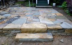Two steps up to a very colorful irregular stone patio.