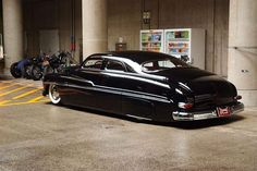 1949 Merc light kustom sedan with a chopped top and flawless black paint job over frenched headlights, rear fender skirts, and wide white wall tires. Pic 2