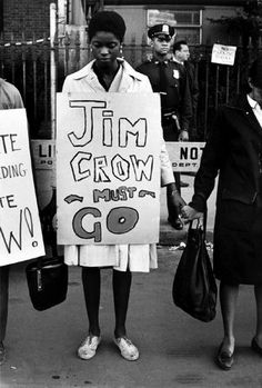 """UNITED STATES—Protesters with placards. One reads """"Jim Crow Must Go,"""" 1962.  © Bruce Davidson / Magnum Photos"""