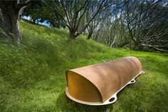 A beautiful coffin - the top lifts off to reveal low sides and a soft sheepskin mattress and pillow.