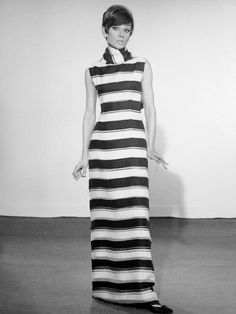 """The actress Audrey Hepburn photographed by Pierluigi Praturlon during a clothing selection for her wardrobe in """"Two for the Road"""". Paris (France), February 1966. Audrey was wearing: Evening gown: Marc Bohan for Miss Dior (of organza, ivory background with stripes in pink and navy blue, of the collection for the Spring of 1966). Earrings: Cartier. Shoes: René Mancini (lined with silk, black and navy blue, of the collection for the Spring/Summer of 1966)."""
