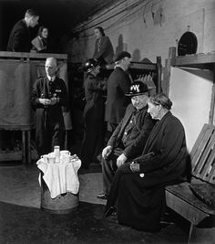 London. June-July, 1941. Home Guard warden and woman share tea in an air-raid shelter.