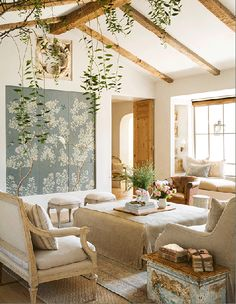 "A Magical Ojai Oasis The couple's self-described ""patina style"" was the title of their first book and the inspiration for their West L.A. shop, Giannetti Home, as well as Brooke's acclaimed Velvet & Linen blog. Natural linen, sisal, and weathered wood give the living room a fresh, unfussy look. Coffee table in Verellen linen and settee in Libeco linen, Giannetti Home; sofa and pillow in Schumacher linen; window seat cushions in Claremont fabrics; wallpaper panels, Gracie; sisal rug, Merida;"