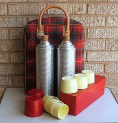 A early 1950s Thermos Brand Vacuum Bottle picnic or stadium set. Two 14 inch vacuum, thermos bottles with original corks and a red plastic sandwich or snack box. Each bottle has 4 nesting cups including the large red cup. Both have original corks.