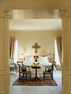A richly carved 18th-century Portuguese crucifix hangs over a Portuguese bed of the same era in this neatly contrasted master bedroom. The intimate foreground sitting area presents the perfect spot for a private breakfast. (Photo: Photo: Jeff McNamara; Designer: Gerrie Bremermann)