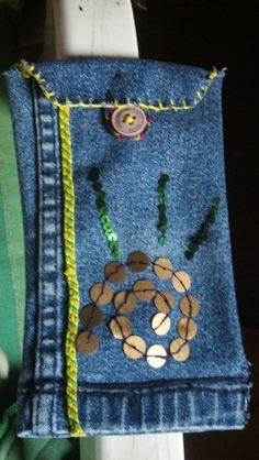 DIY Denim pouch... Used an old pair of Jeans for this.. Braided thread bracelets and sequins can be used for decoration....