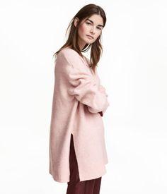 Pudderrosamelert. En strikket, oversized genser i melert garn med ull. Genseren har rund halsringning og lange ermer med lav skuldersøm. Splitt i sidene.