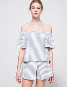 From Farrow, a woven striped cropped top in white and blue stripes. Features off-the-shoulder neckline, short sleeves, flare sleeves, round high-low hem, cropped length and casual fit. • Woven striped cropped top • White and blue stripes pattern •