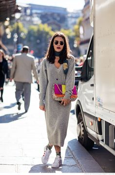 Try a sweater dress, burgundy-stained lip, round frame sunglasses, colorful clutch, silk scarf doing double duty as a necklace, and stan smith sneakers