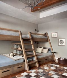 Custom bunk beds were designed for comfort and ease of use. Warm accents include Phillip Jeffries' Tweed Wall covering and a large patchwork sheepskin rug by Mike Ragan Home. CP Lighting's New Growth Chandelier adds a chic yet rustic touch.