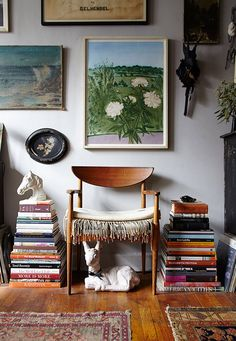 A beautiful mid-century chair, stacked books, a gallery wall, and whimsical animals. Love.
