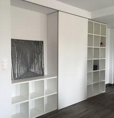 Recibidor con armario y estantería a la derecha. La puerta corredera esconde un guardarropa, esta misma puede ocultar el recibidor o la estantería.