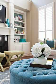 What's not to love! Built in shelves, fire place, shutters, tufted ottoman and hydrangeas.