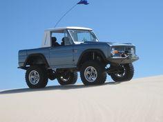 Blue half cab classic ford bronco in the dunes