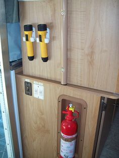 Broom clips to hold flashlights near the door of your camper