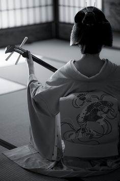 A geiko playing on the shamisen (instrument like guitar, 3 strings)
