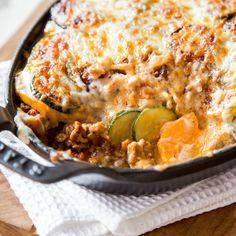Buntes Moussaka -geschichtet in einem heißen Auflaufzwischen Fleisch, Béchamel-Sauce und Gouda fühlen sich Zucchini und Süßkartoffel pudelwohl.