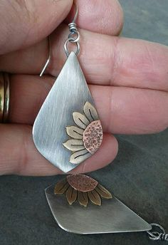This beautiful pair of sunflower earrings is made by me. Each piece is hand cut by me using sterling silver, brass, and copper and is soldered in place. This pair measures 2 3/8 inches in length from the top of the ear wire to the bottom of the dangle. They have been oxidized to show